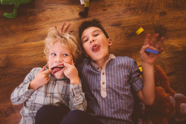 Two boys making funny faces while playing on the floor stock photo