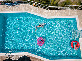 Two boys on inflatable floats in the swimming pool