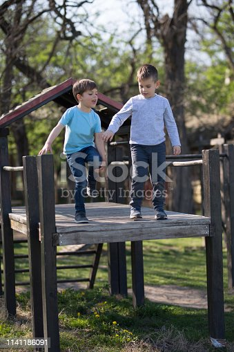 Two boys on playground ready to jump