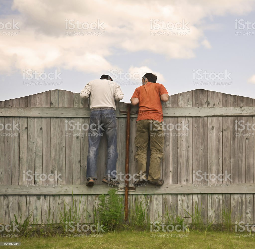 Two boys on the fence looking for smth stock photo