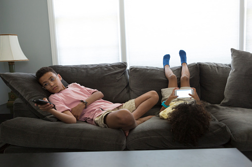 Two boys sit on a couch.  The older boy is 12 years old and has glasses, a pink shirt and shorts.  The younger boy is 6 years old, he has big natural hair and is sitting upside down on the couch and playing with his phone.  The older boy reclines and holds a television remote.  Both boys are hispanic.