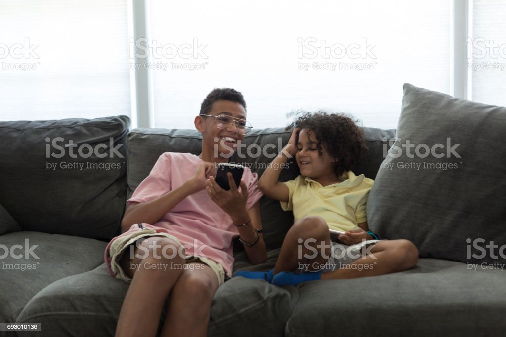 Two lads boning around on a sofa