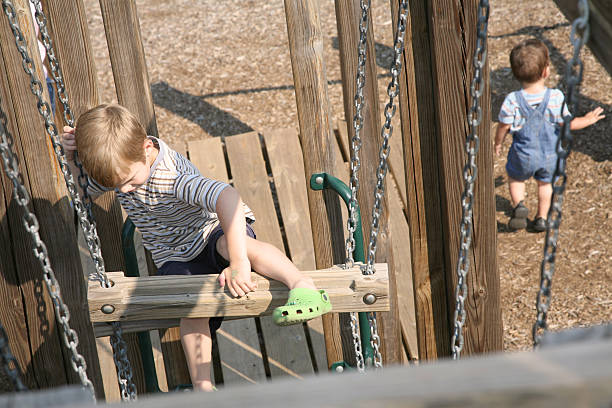 zwei jungen spielen am spielplatz - arbeiten von schülern aufhängen stock-fotos und bilder