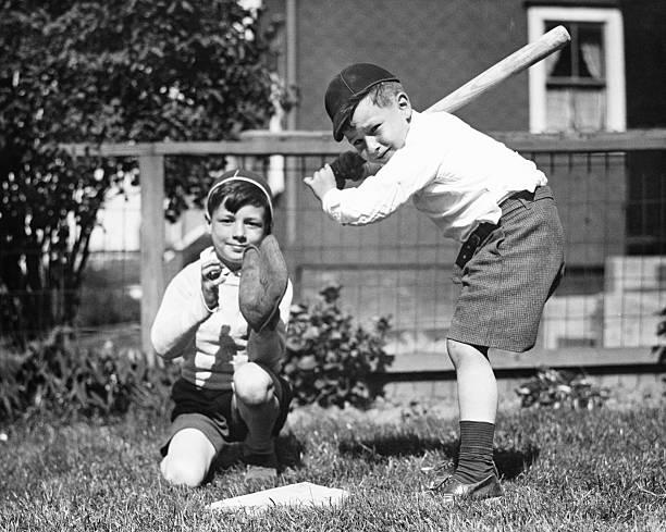Two boys (6-7) playing baseball in garden, (B&W) stock photo