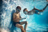Two boys playing digital tablet underwater
