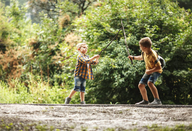 Two boys playing fight with wooden swords.Childhood concept. stock photo