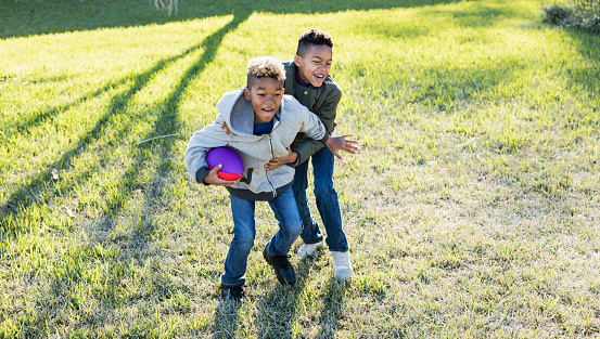 istock Two boys playing football in back yard 920736050