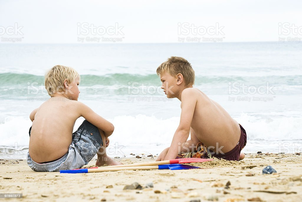 Two boys playing on beach. royalty-free stock photo
