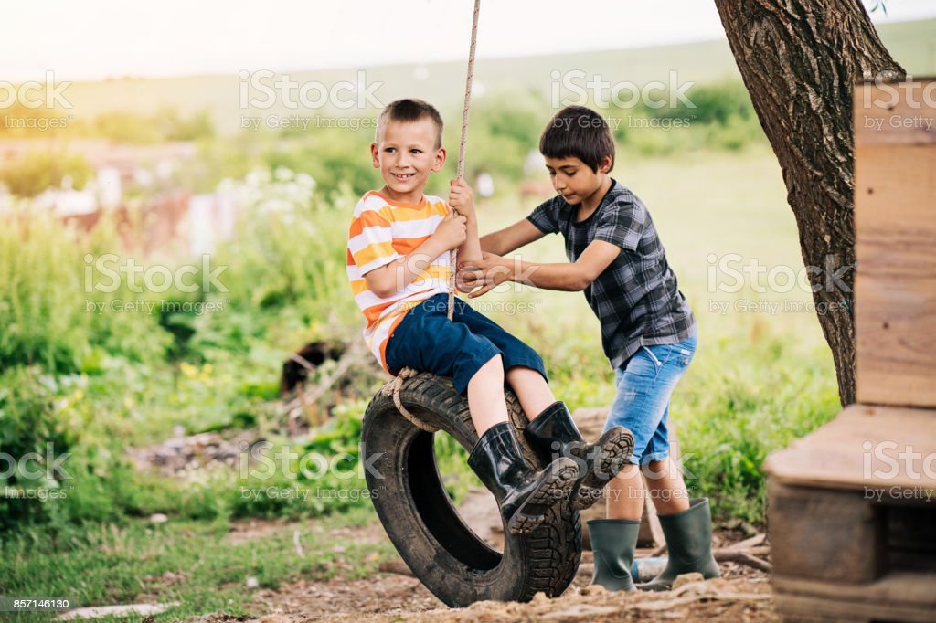 Two boys playing with a tire swing stock photo