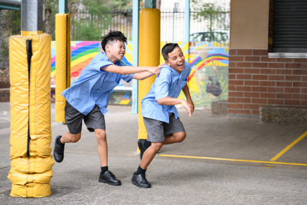 Two boys running and laughing in school playground stock photo