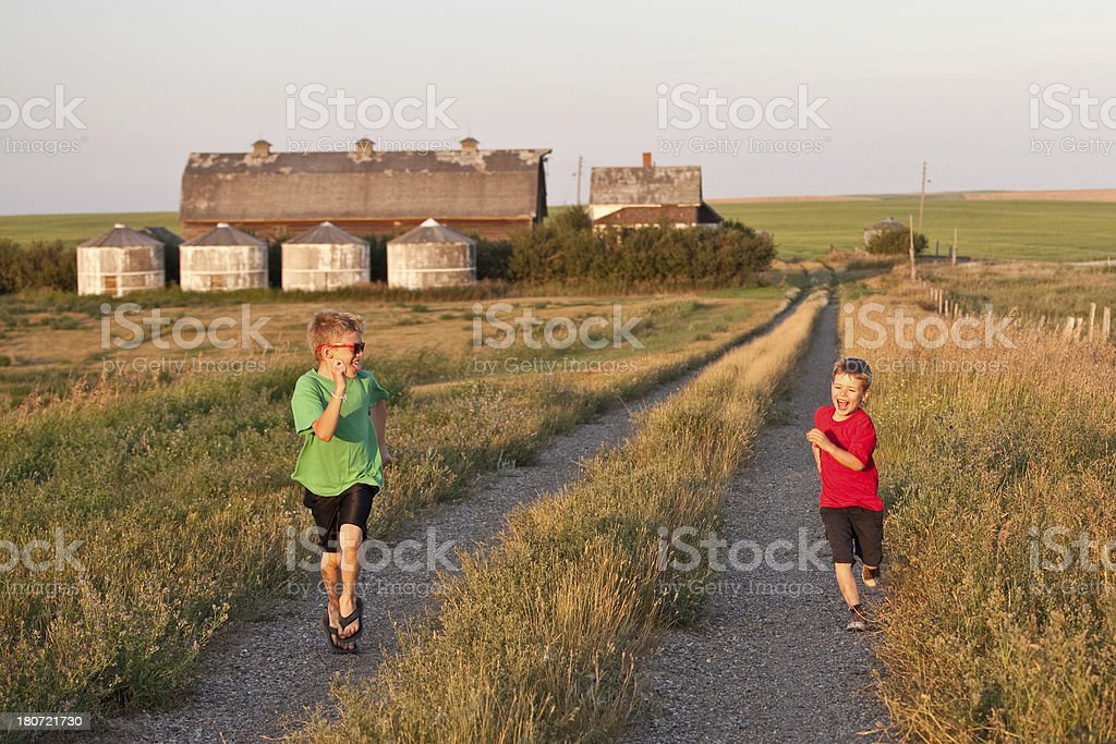 Two Boys Running Down a Country Road royalty-free stock photo