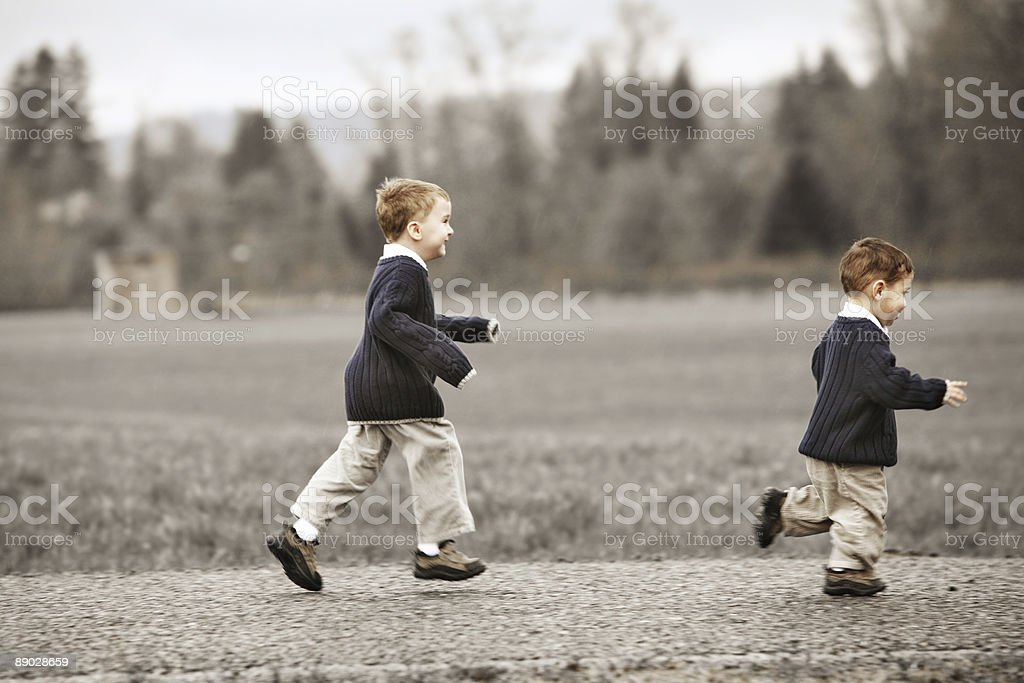 Two Boys Running Down a Gravel Road royalty-free stock photo