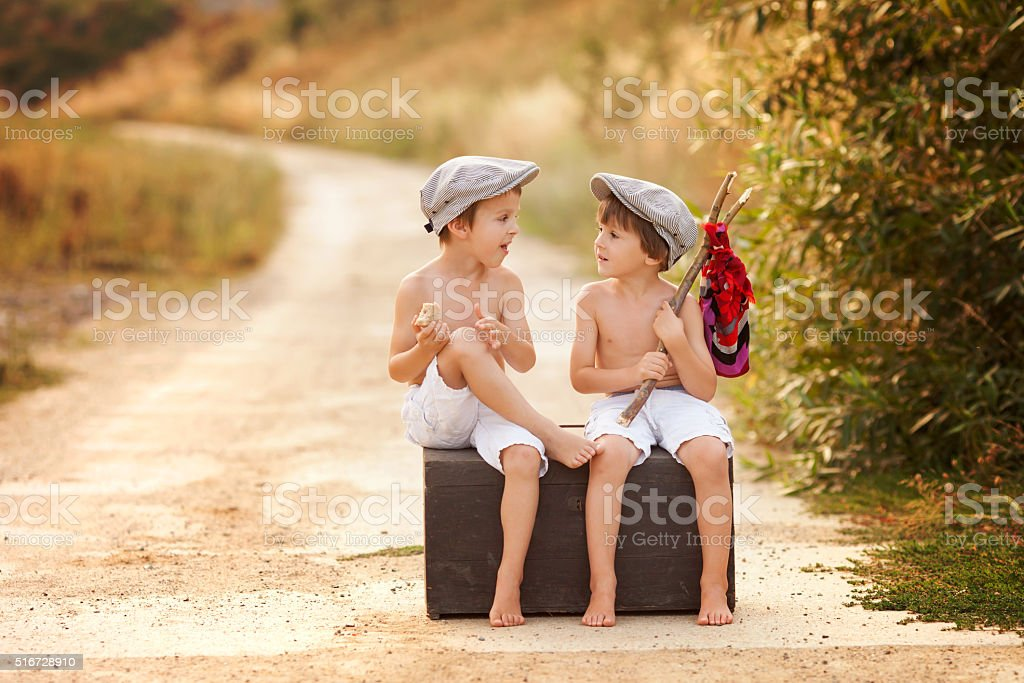 Two boys, sitting on a big old vintage suitcase, playing stock photo