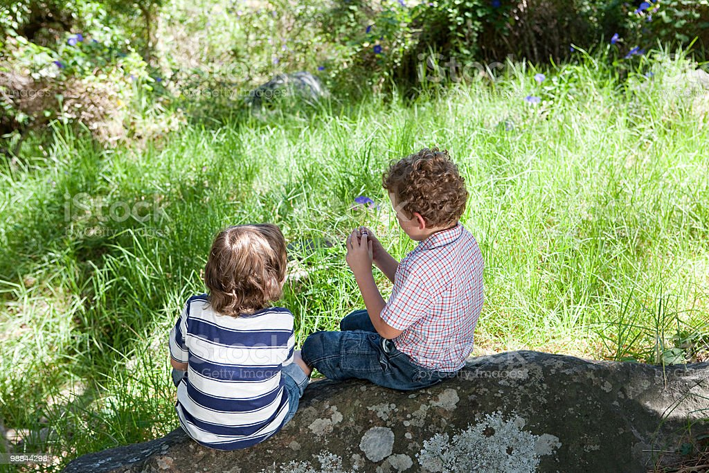 Two boys sitting on a rock royalty-free stock photo