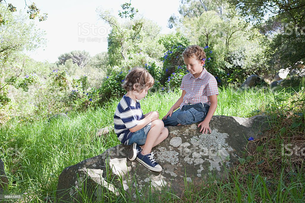 Two boys sitting on a rock royalty free stockfoto