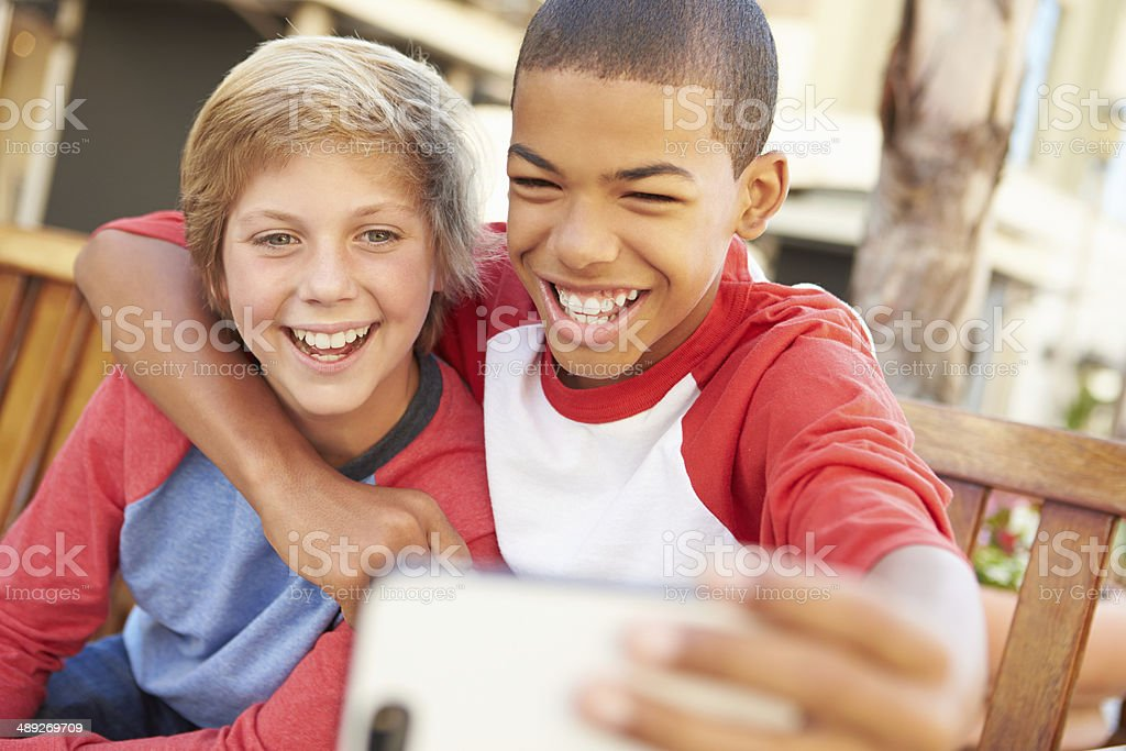 Two Boys Sitting On Bench In Mall Taking Selfie royalty-free stock photo