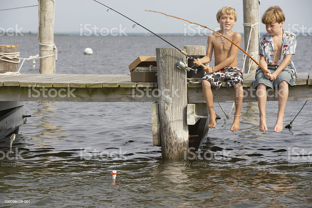 Two boys (7-9) sitting on jetty, fishing royalty-free stock photo