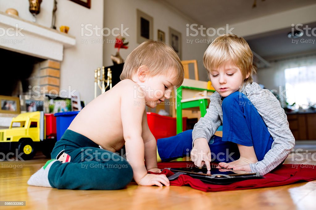 Two boys sitting on the floor playing on tablet. photo libre de droits