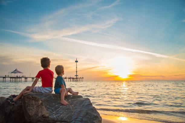 Zwei Jungs sitzen bei Sonnenuntergang auf dem Felsen am Strand – Foto