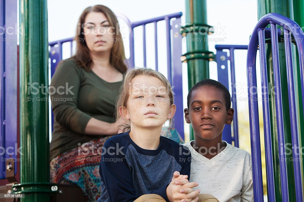 Two boys sitting with mother at playground stock photo