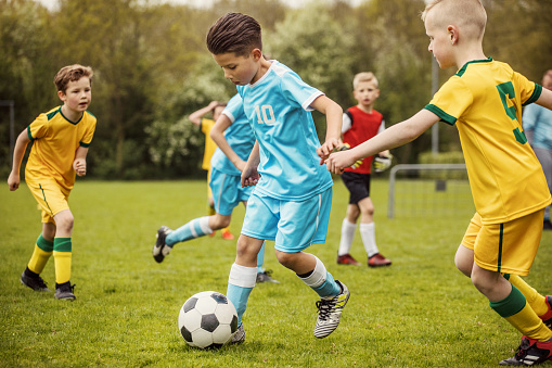 istock Two boys soccer teams competing for the ball during a football match 961323802