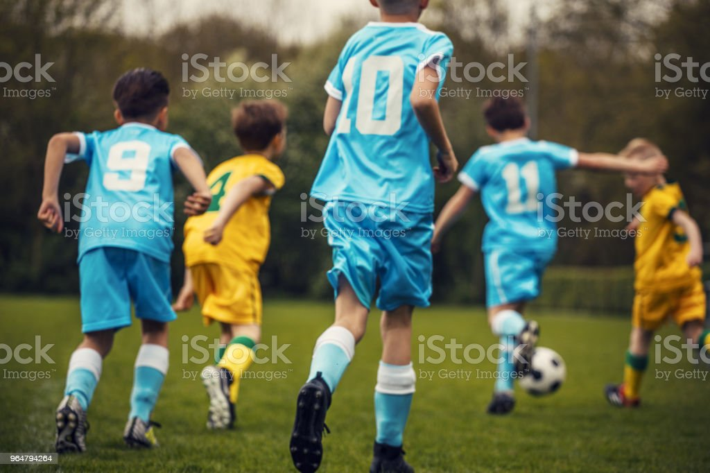 Two boys soccer teams competing for the ball during a football match