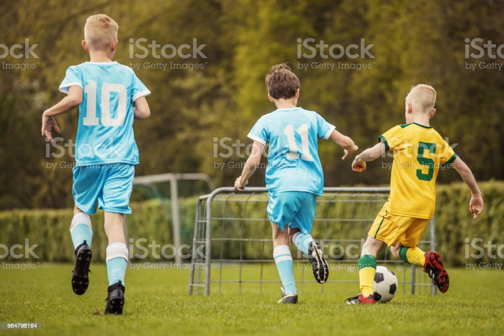 Two boys soccer teams competing for the ball during a football match royalty-free stock photo