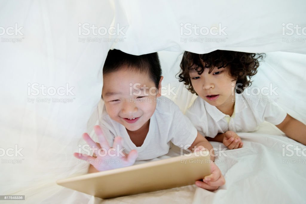 Two boys using digital tablet under the covers stock photo