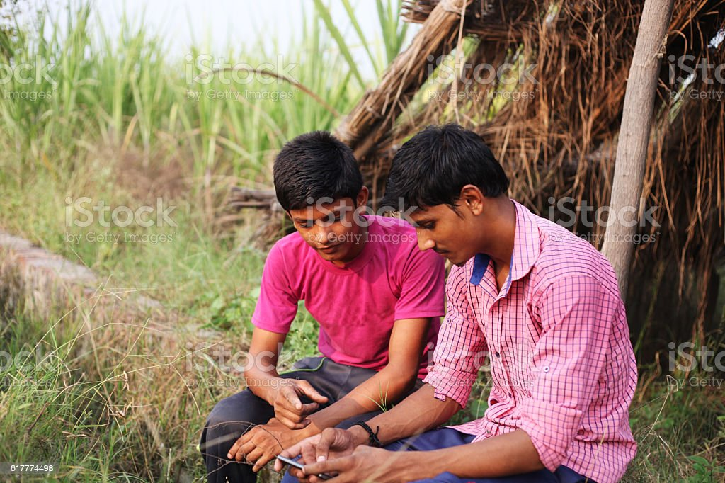 Two boys using Smartphone and text messaging stock photo