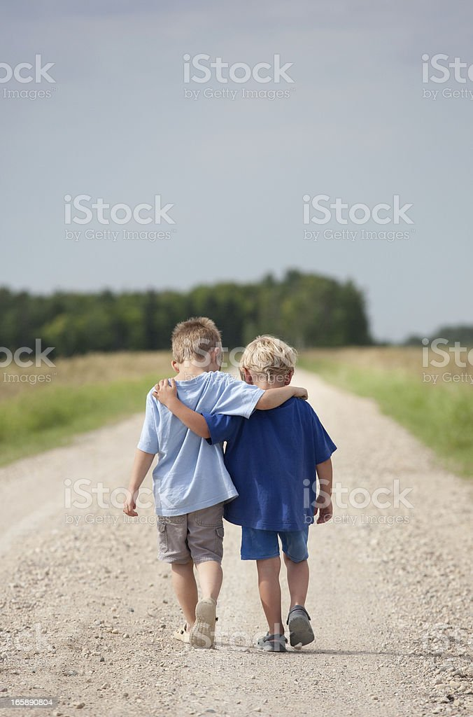 Two Boys Walking Down a Gravel Road stock photo