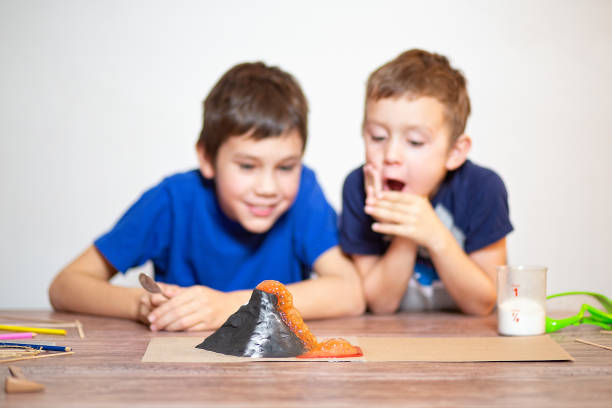 Two boys watching a chemistry experiment volcanic eruption. school science project. children surprised. Chemical reaction of baking soda and vinegar. Selective focus volcano stock pictures, royalty-free photos & images