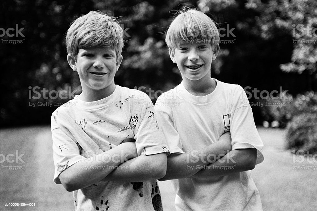 Two boys (10-11) with arms crossed, outdoors, portrait (B&W) royalty-free stock photo