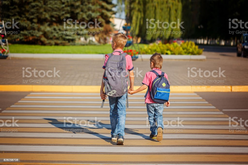 Two boys with backpack walking, holding on warm day  on the road stock photo