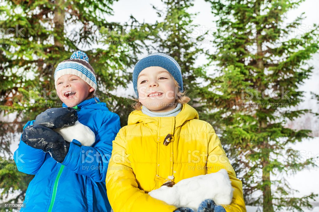 Two boys with big chunk of snow in the park stock photo