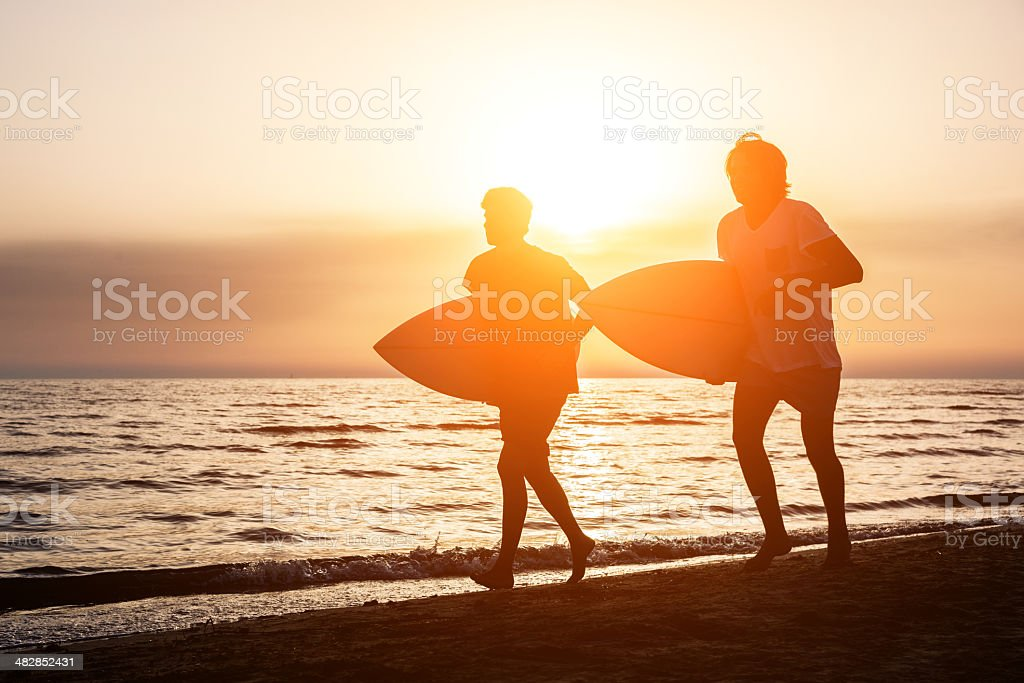 Two Boys with Surf Boards at Sunset stock photo