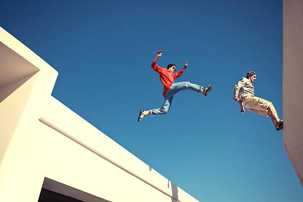 zwei mutige männer springt auf dem dach - parkour stock-fotos und bilder