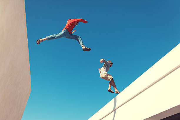two brave men jumping over the roof - daredevil stock pictures, royalty-free photos & images