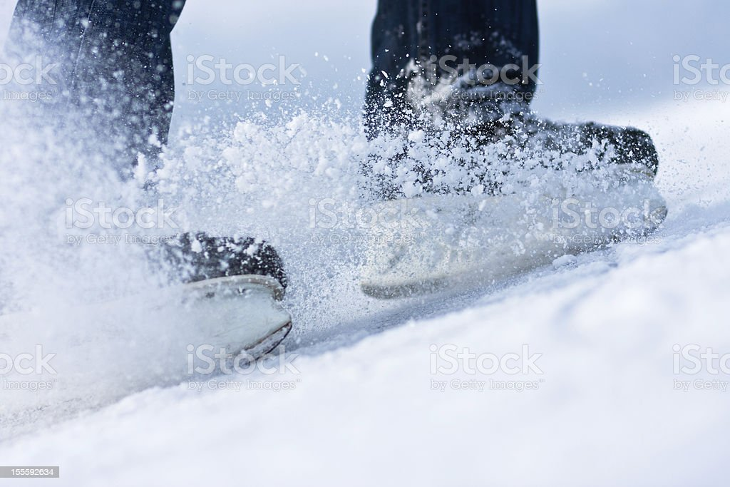 Two breaking ice skates with flying snow stock photo