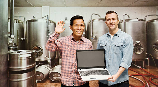Two brewmaster working with laptop in industry stock photo