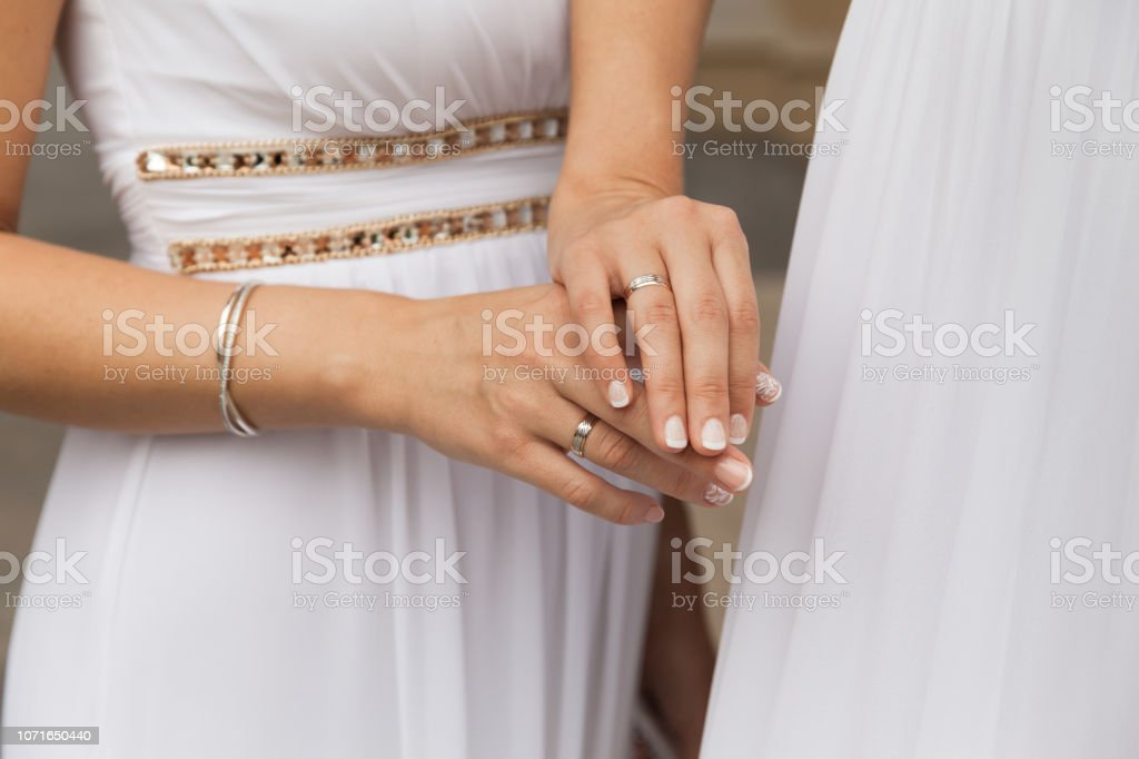 Two Brides In White Dresses Showing Wedding Rings stock photo