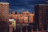 Two Bridges neighborhood. Roof tops of historic apartments in New York. High-rise and walk-up buildings under autumn stormy sky. Red brick walls with rows of windows in Lower East Side.