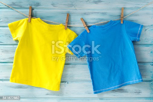 istock Two bright baby t-shirts hanging on a clothesline on a wooden background 541822662