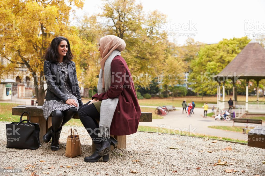 Two British Muslim Women Meeting In Urban Park stock photo