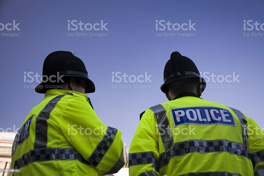 Two British Policemen wearing Traditional Helmets-Click below for more. stock photo