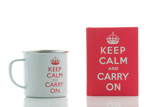 London, England-March 18, 2011.  Two British souvenirs with the famous historical phrase on them to Keep Calm and Carry On.  The souvenirs are a white metal coffee mug and a small red book filled with quotes about keeping calm and carrying on.