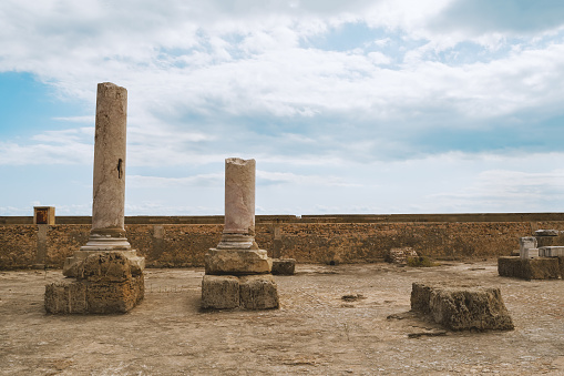 Two broken columns of ancient Carthage in Tunisia against the sky.