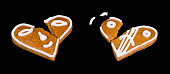 istock Two broken gingerbreads in a heart shape with painted smiley face isolated on a black background 1277027072
