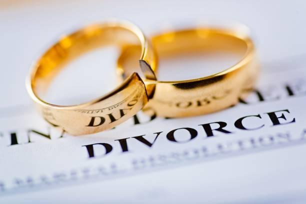 Two broken golden wedding rings divorce decree document stock photo