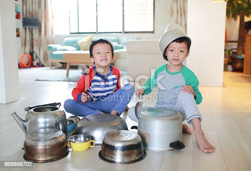 505657693 istock photo Two brother playing on floor with pots and pans 868866702