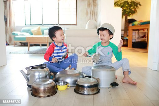 505657693 istock photo Two brother playing on floor with pots and pans 868866720